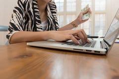 Affärs- och finansbegrepp, affärskvinna som rymmer kassa och använder bärbara datorn för E-kommers online-shopping royaltyfria foton