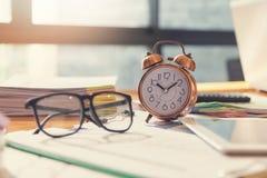 Affärs- och finansbegrepp av kontorsarbete, Closeupklockan och glasögon på kontorsskrivbordet arkivfoto