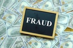 Affärs- och finansbegrepp Bästa sikt av svart tavla som är skriftlig med BEDRÄGERI med hundra dollarsedel på bakgrunden royaltyfri foto