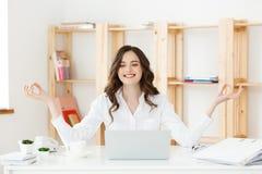 Affärs- och hälsobegrepp: Ung kvinna för stående nära bärbara datorn, praktiserande meditation på kontorsskrivbordet som är främs royaltyfri fotografi