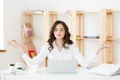 Affärs- och hälsobegrepp: Ung kvinna för stående nära bärbara datorn, praktiserande meditation på kontorsskrivbordet som är främs royaltyfri bild