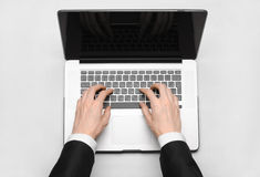 Affärs- och teknologiämne: handen av mannen i en svart dräktvisninggest mot en grå färg- och vitbakgrundsbärbar dator i set Royaltyfri Foto