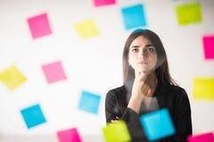 Affärs-, start-, planläggnings-, ledning- och folkbegrepp - lycklig idérik kvinnahandstil på klistermärkear på det glass brädet f royaltyfria foton