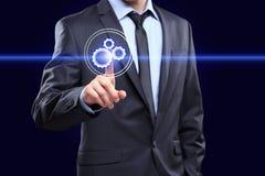 Affärs-, teknologi- och internetbegrepp - trängande knapp för affärsman med mekanismsymbolen på faktiska skärmar Royaltyfri Foto