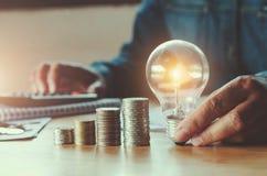 affärsaccountin med sparande pengar med den hållande lightbulben för hand arkivbild