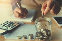 affärsaccountin med sparande pengar med handen som in sätter mynt royaltyfri bild