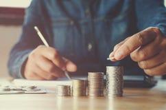Affärsaccountin med sparande pengar med handen som sätter på mynt royaltyfri bild