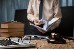 Affärsadvokat som hårt arbetar på arbetsplatsen för kontorsskrivbord med boken Royaltyfri Fotografi