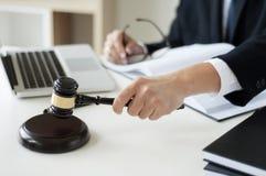 Affärsadvokathand som rymmer rättvisahammaren på kontoret med bärbara datorn, boken och dokument arkivbild