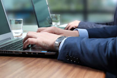 Affärsarbetarna på skrivbord med en bärbar dator i upptaget idérikt av Royaltyfri Fotografi