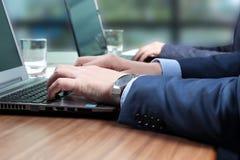 Affärsarbetarna på skrivbord med en bärbar dator i upptaget idérikt av Royaltyfri Bild