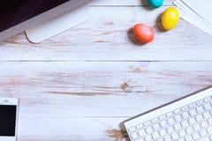 Affärsarbetsskrivbordet med lyckliga easter semestrar mångfärgad äggbakgrund royaltyfria foton