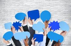 Affärsarmar som lyfts med anförandebubblan av tegelstenväggen Arkivfoto