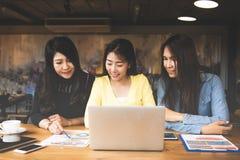Affärsasia kvinnor blir partner med att diskutera grafen av finansiellt i arbetsutrymme, tillfällig dräkt royaltyfri bild