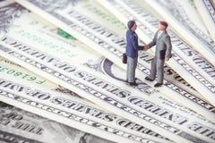 Affärsavtal eller överenskommelse- och framgångbegrepp Två miniatyraffärsmän som skakar händer, medan stå på amerikanska dollarpe arkivfoton