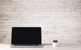 Affärsbärbar dator med den vita tegelstenväggen Arkivfoto
