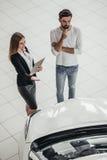Affärsbiträde med kunden i bilåterförsäljare Arkivfoton