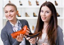Affärsbiträdet erbjuder höjdpunkten heeled skor för kunden fotografering för bildbyråer