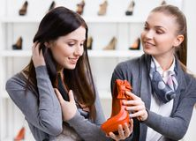 Affärsbiträdet erbjuder skodon för kunden arkivfoto