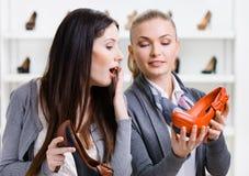 Affärsbiträdet erbjuder stilfulla pumpar för kunden royaltyfria foton
