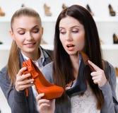 Affärsbiträdet erbjuder stilfulla skor för kunden arkivbild