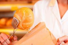 Affärsbiträdet packar bröd i bageri Arkivbilder