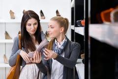 Affärsbiträdet visar höjdpunkten heeled skor till kunden royaltyfria bilder