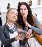 Affärsbiträdet visar skodon till kunden Arkivbilder