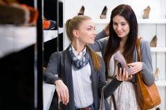 Affärsbiträdet visar stilfulla skor till kunden Royaltyfri Foto