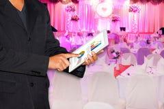 Affärsbröllop, bröllopaffärsman som använder minnestavlan och suddig bakgrund royaltyfri bild