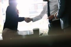 Affärsbundsförvanter som skakar händer efter ett avtal arkivfoton