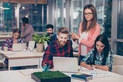 Affärschef som kontrollerar finansiell uppgift av hennes kollegor Smarta klyftiga intelligenta kollegor som diskuterar det nytt,  arkivfoto