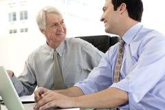 Affärschefer som till varandra ler Fotografering för Bildbyråer
