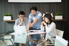 Affärscoworkers som i regeringsställning diskuterar i mötesrum arkivfoto