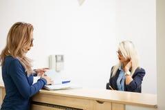 Affärsdam med hennes blonda sekreterare i det väntande området av a Arkivfoto
