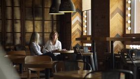 Affärsdam Meeting med klienten i kaffehus lager videofilmer