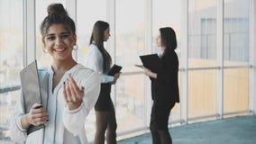 Affärsdam på kontoret som talar till en smartphone Lycklig le caucasian upptagen affärskvinna arkivfilmer