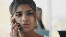 Affärsdam på kontoret som talar till en smartphone Lycklig le caucasian upptagen affärskvinna lager videofilmer