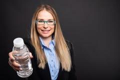 Affärsdam som bär blåa exponeringsglas som erbjuder flaskan av vatten Arkivfoto