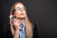 Affärsdam som bär blåa exponeringsglas som kyler med flaskan av vatten Fotografering för Bildbyråer