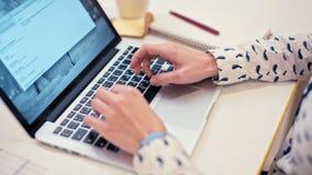 Affärsdamen arbetar på bärbara datorn i en hemtrevlig text för kontorsrummaskinskrivning lager videofilmer