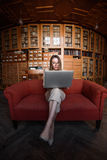 Affärsdamen sitter på den röda soffan och arbetar i hennes bärbar dator fotografering för bildbyråer