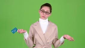 Affärsdamen som rymmer en kreditkort i hennes händer, har inga pengar grön skärm stock video