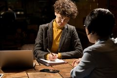 Affärsdamer som skriver plan av arbete i mörkt kontor royaltyfria bilder