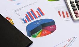 Affärsdiagram och grafer med boken och räknemaskinen Arkivbild