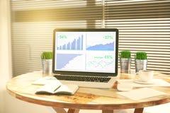 Affärsdiagram på bärbar datorskärmen med dagboken, hinkar av gräs och Royaltyfri Bild