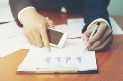 Affärsdokument på kontorstabellen med den smarta telefonen och mannen arbetar royaltyfri bild