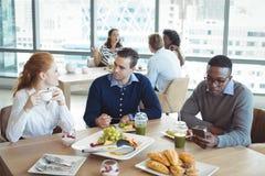 Affärsentreprenörer som i regeringsställning sitter på frukosttabellen Arkivfoton