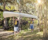 Affärsföretag som två älskar män som bär en kanot in i en flod royaltyfria bilder