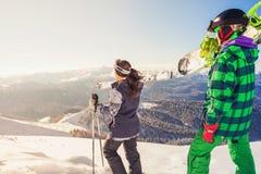 Affärsföretag till vintersporten Skidåkare och snowboarder som fotvandrar på berget Arkivbilder